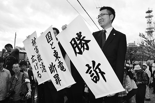 ▶勝訴の旗を掲げる原告側の弁護士、福島地裁前。