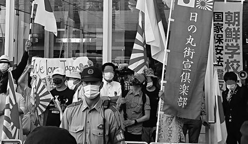 市職員が立ち会う中で行われたヘイト宣伝。手前は機動隊員。「朝鮮学校は国家保安法違反」のノボリ旗も見える(7月12日、編集部撮影)。